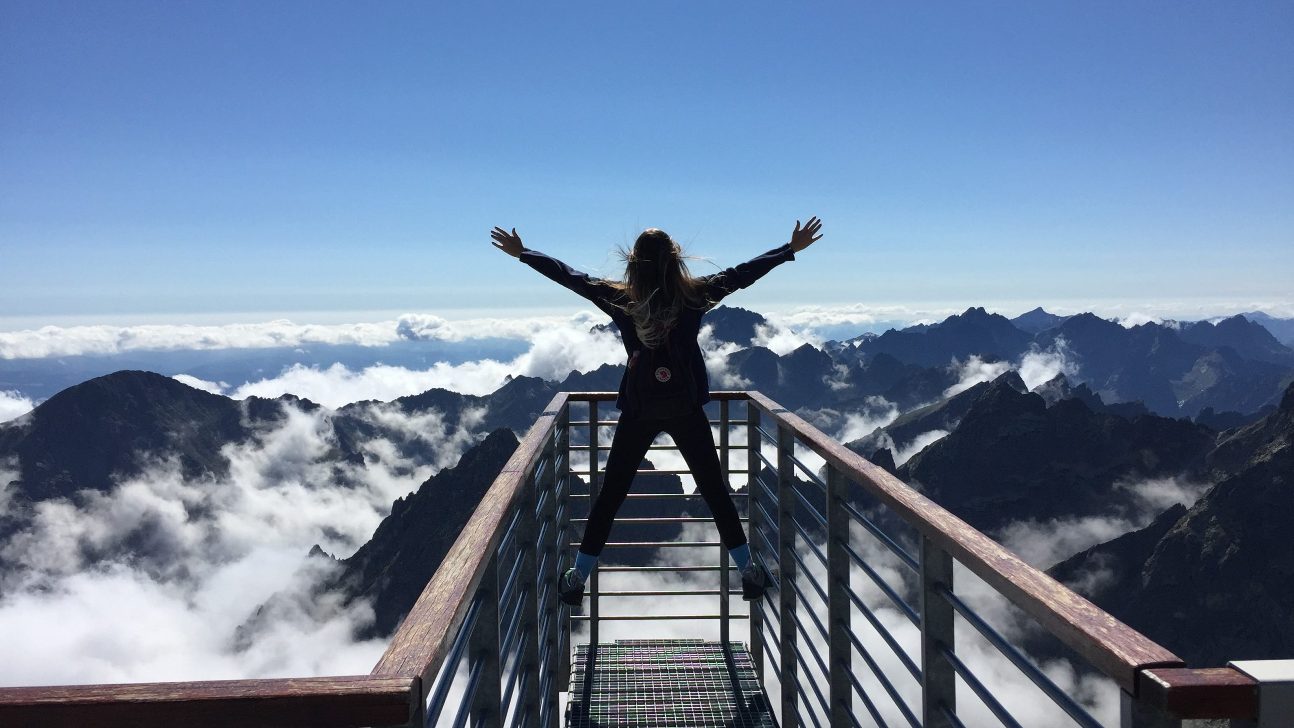 Person standing on hand rails with arms open facing the mountain.